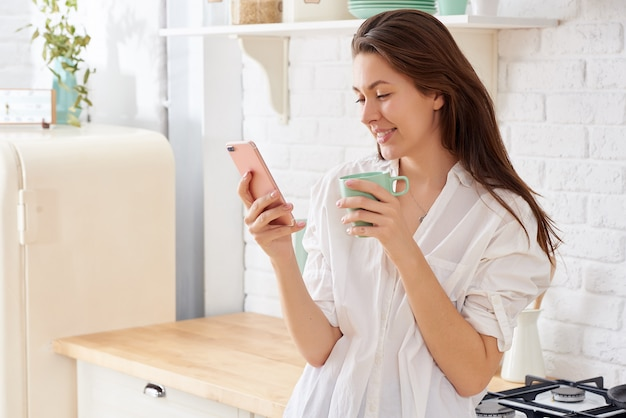 Young woman using smartphone leaning at kitchen table with coffee mug and organizer in a modern home.