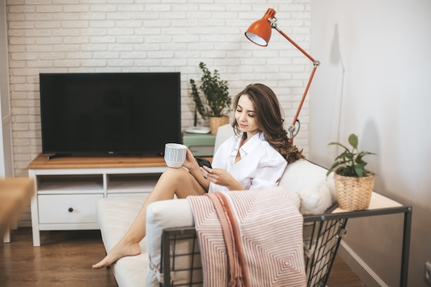 Young woman using smartphone sitting on couch at home. young person drinks coffe in big mug and serfing internet
