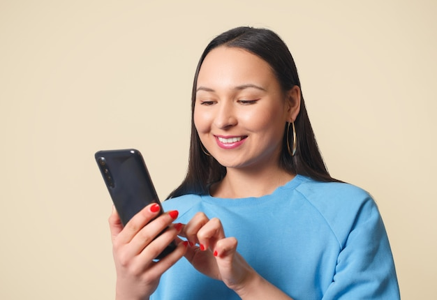 Young woman using smartphone and smiling. on a cream background.
