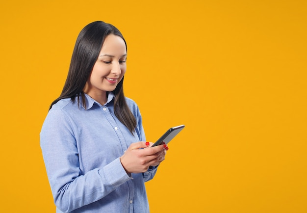 Young woman using smartphone and smiling. on a yellow background.