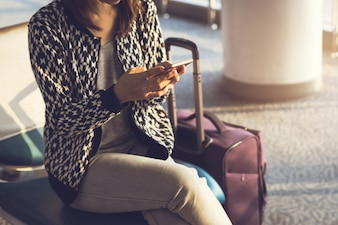 Young woman using smartphone while waiting at the airport