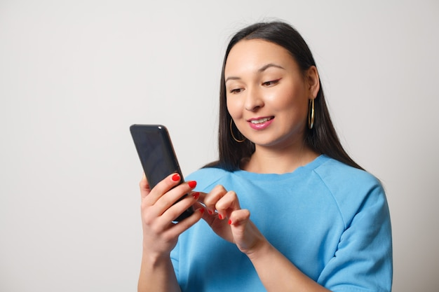 Young woman using a smartphone. on a white background.
