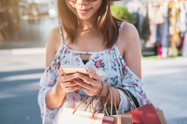 Young woman using smartphone with shopping bags at shopping mall on black friday, woman lifestyle concept