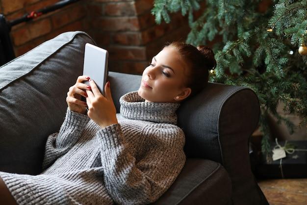 젊은 여자는 소파에 태블릿을 사용 하여