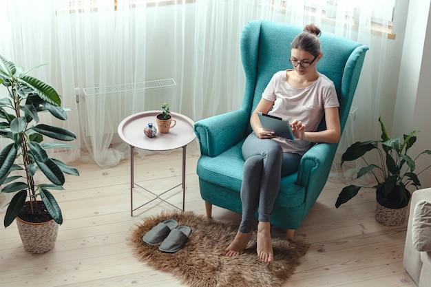 편안한 의자에 앉아있는 동안 태블릿을 사용하는 젊은 여자