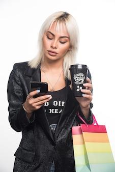 ギフトバッグとカップを保持しながら電話を使用して若い女性。高品質の写真
