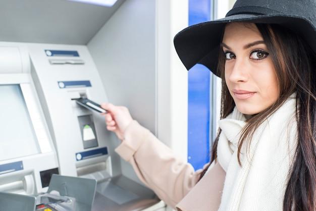 Молодая женщина, использующая банкомат