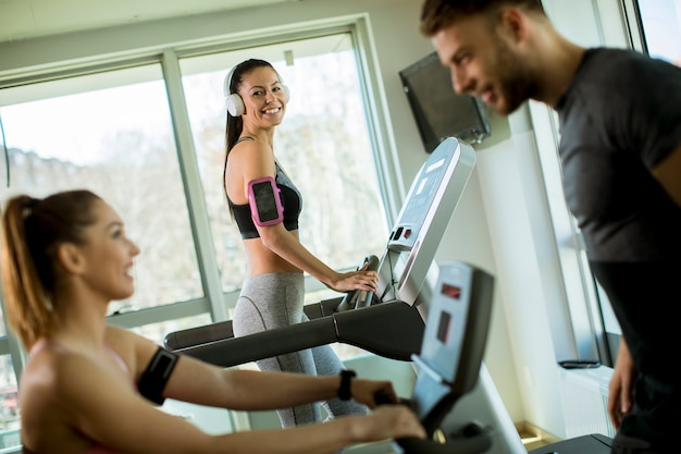 Young woman using treadmill in modern gym
