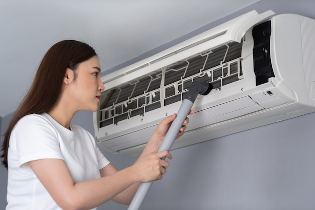 Young woman using vacuum cleaner to cleaning the air conditioner at home