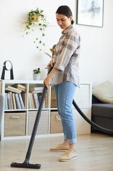 家事に掃除機を使っている若い女性が自宅の床を掃除機で掃除している