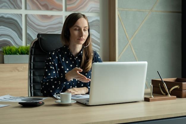 Молодая женщина с помощью видеочата на ноутбуке в офисе