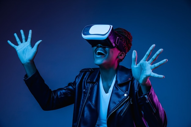 Young woman using vr glasses in neon light