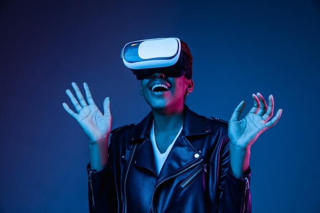 Young woman using vr-glasses with neon lights