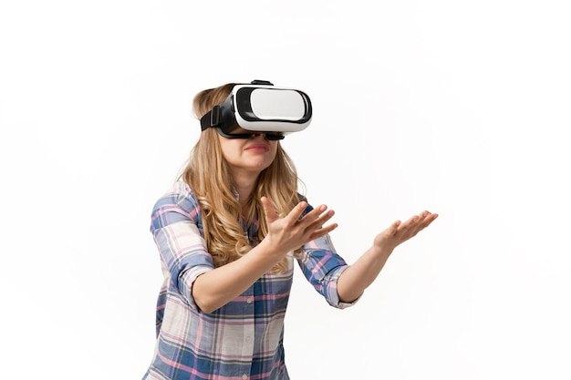 Young woman using vr-headset devices, gadgets isolated on white studio wall