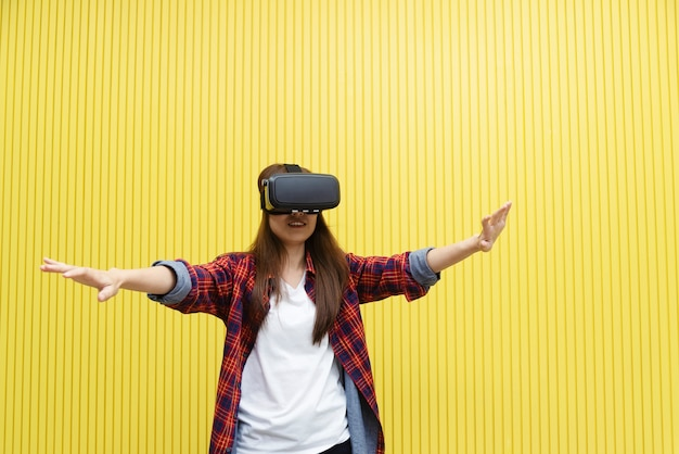 Young woman using vr on yellow room. future technology for life.
