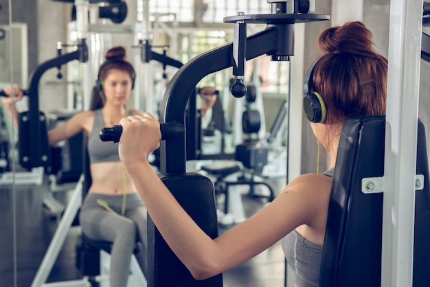 Young woman using weight lifting equipment to build a massive chest and arm at indoor sport gym.