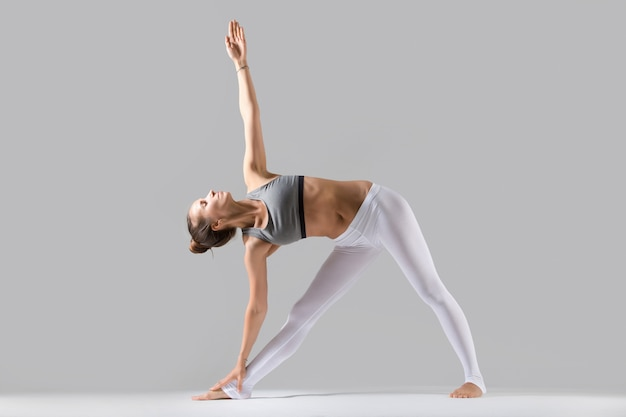 Young woman in utthita trikonasana pose, grey studio background