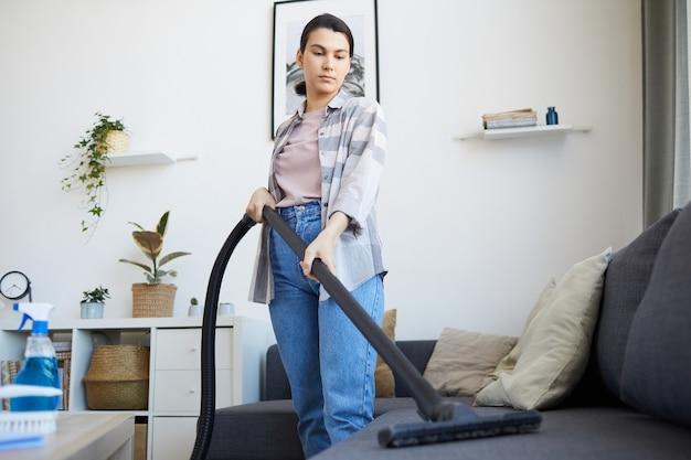 居間で掃除機でソファを掃除機で掃除する若い女性