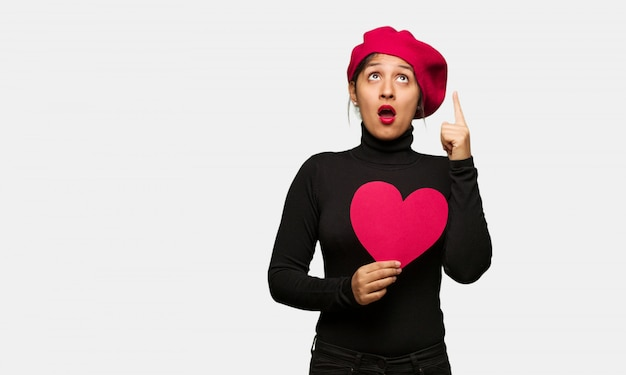 Young woman in valentines day surprised pointing up to show something