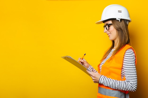 Young woman in a vest and hard hat holds a clipboard and takes notes on a yellow