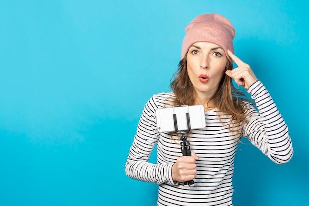若い女性のビデオブロガーは、三脚に電話を持ち、青い表面で思考ジェスチャーをします