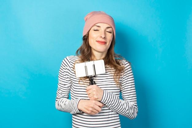若い女性のビデオブロガーは、青い表面の三脚に電話を保持します