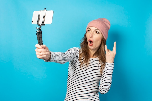 若い女性のビデオブロガーは、青い表面で放送しながら電話で自分の写真を撮ります