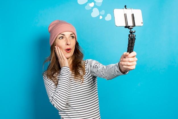 若い女性のビデオブロガーは、青い壁で放送しながら電話で自分の写真を撮ります。コンセプトストーリー、vlog、selfie、ブログ。