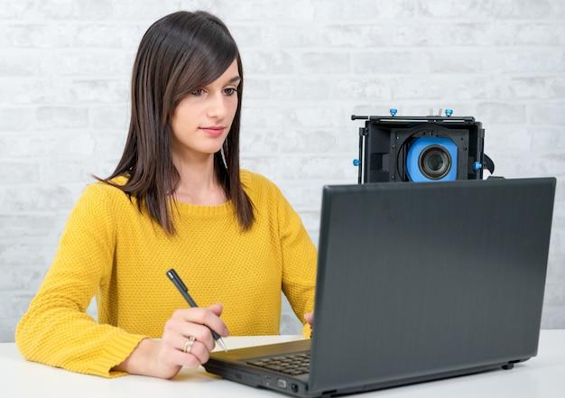 Young woman video editor working in studio