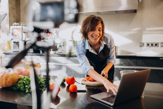Видеоблогер молодой женщины готовит на кухне и снимает