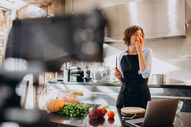 Young woman videoblogger cooking at the kitchen and filming
