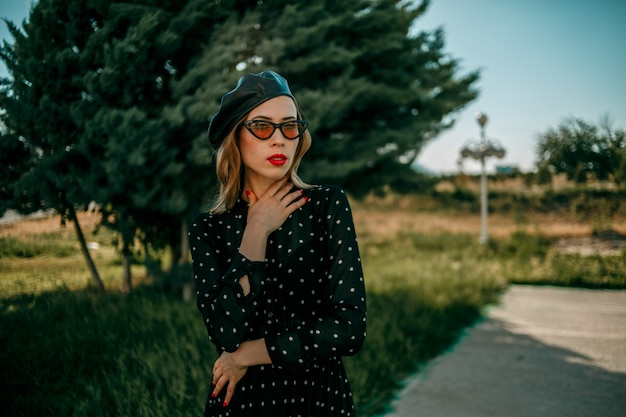 Young woman in vintage black polka dot dress posing outside
