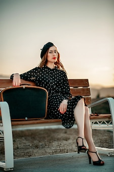 Young woman in vintage black polka dot dress with retro suitcase in hand posing outside