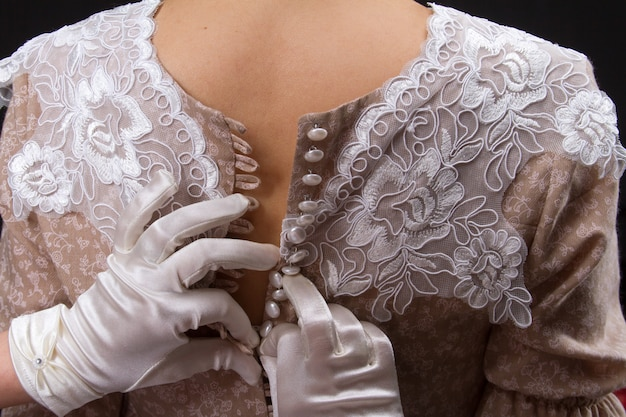 A young woman in vintage lingerie and white gloves unzips her girlfriends dress, a lot of buttons.