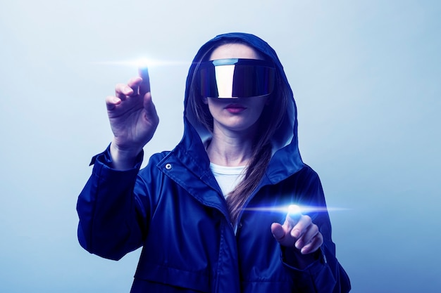 Young woman in virtual reality glasses pressing her finger on the touchscreen, added gradient on a light background.