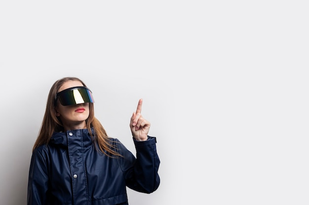 Young woman in virtual reality glasses shows a thumb up on a light background.