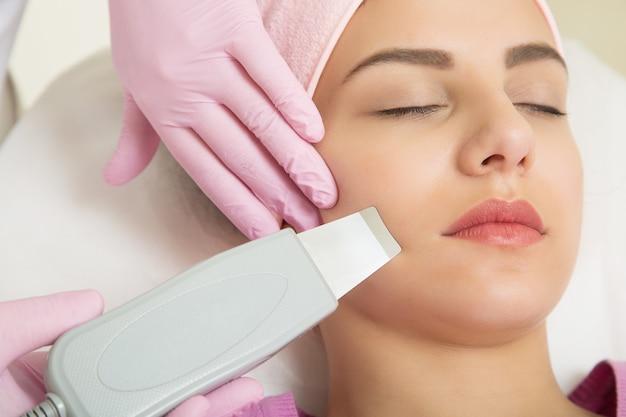 Молодая женщина сегодня посещает косметолога. инструмент в руке