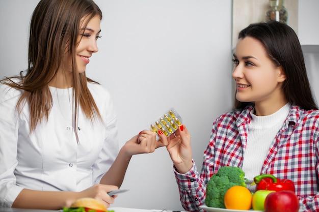 Диетолог молодой женщины посещая в клинике потери веса