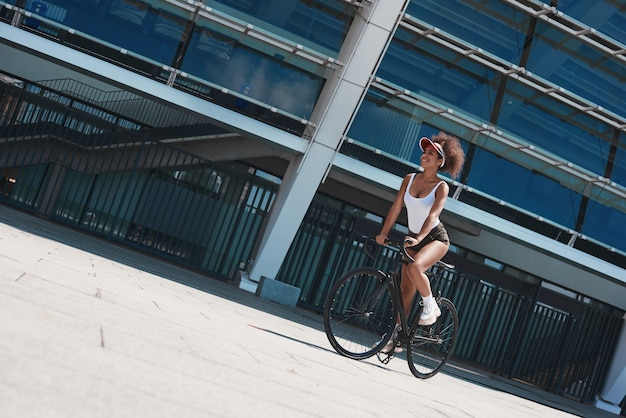 Young woman in visor free style on the street riding bicycle che