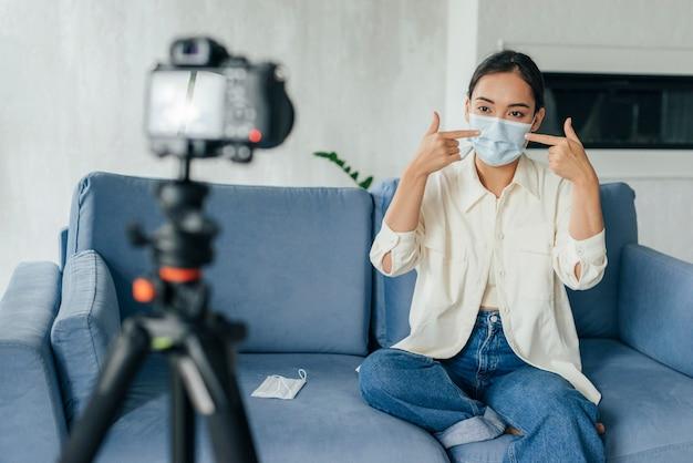 医療用マスクについてビデオブログをしている若い女性