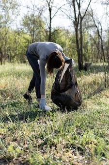 Молодая женщина-волонтер собирает мусор в парке. концепция защиты окружающей среды от мусора. загрязнение планеты