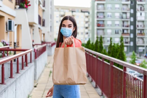 의료 마스크와 젊은 여자 자원 봉사 음식과 야채와 함께 종이 봉지를 들고있다. 격리, 코로나 바이러스 격리를 돕는 기부.