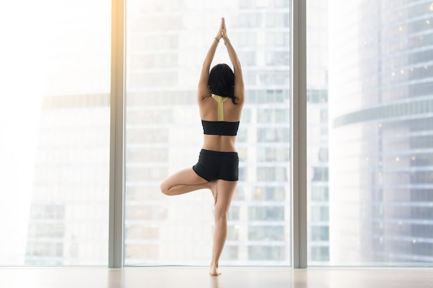 Young woman in vrksasana pose against floor window, rear view