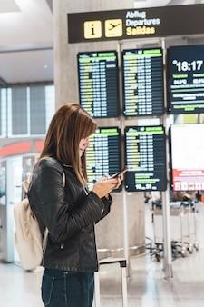 若い女性が待っていると彼女の携帯電話で空港で彼女のフライトをチェックします。旅行と休暇の概念。