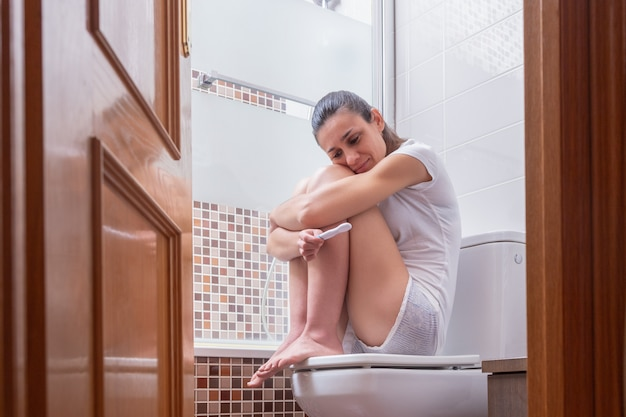 Young woman, waiting calmly for the result of the pregnancy test in the bathroom at home