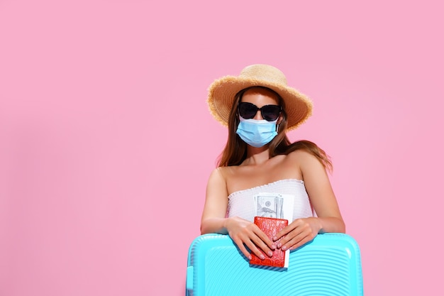 Young woman waiting for flight sitting on floor near her suitcase wearing face mask to prevent coron...