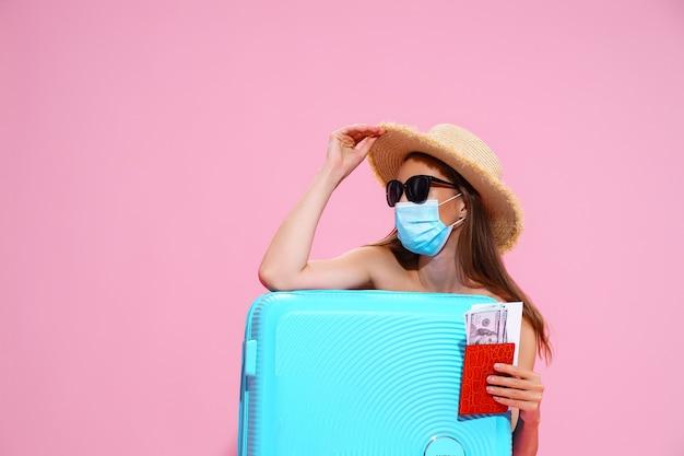 Молодая женщина в ожидании рейса сидит на полу возле своего чемодана в маске для предотвращения коронавируса.