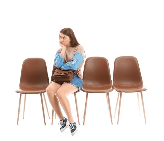 화이트에 그녀의 차례를 기다리는 젊은 여자 프리미엄 사진