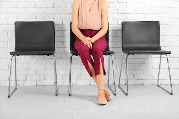 Молодая женщина ждет собеседования в помещении