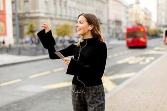 都市の通りにタクシーまたはバスを待っている若い女性